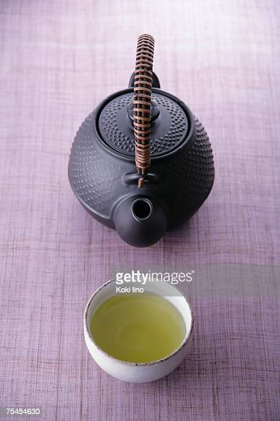 A cup of green tea and teapot