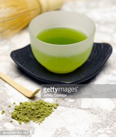 Cup of green tea with matcha powder on side, studio shot : Stock Photo