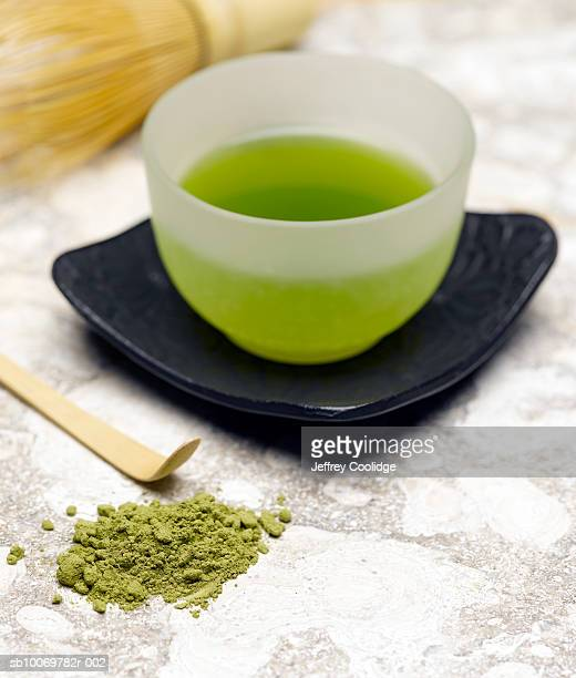 Cup of green tea with matcha powder on side, studio shot