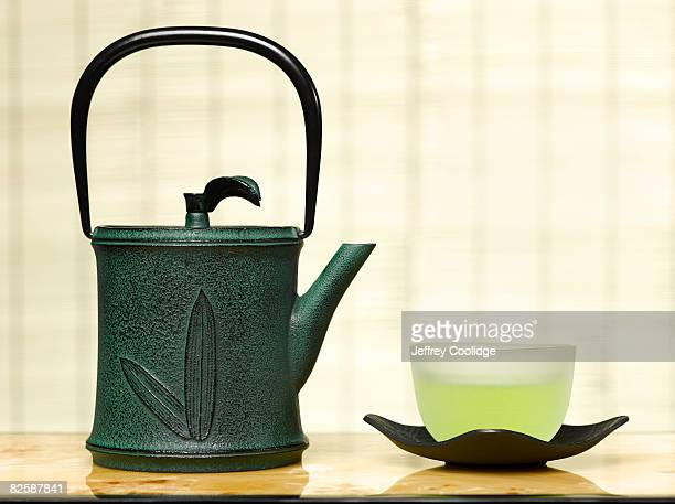 Cup of green tea with teapot