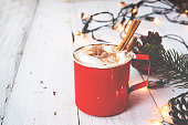 Christmas background - Cup of hot chocolate on wood table with rustic decoration and Christmas lights. vintage color tone style.