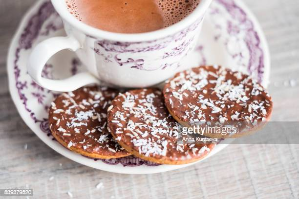 Cup of hot chocolate or cocoa and cookies with chocolate and coconut, selective focus