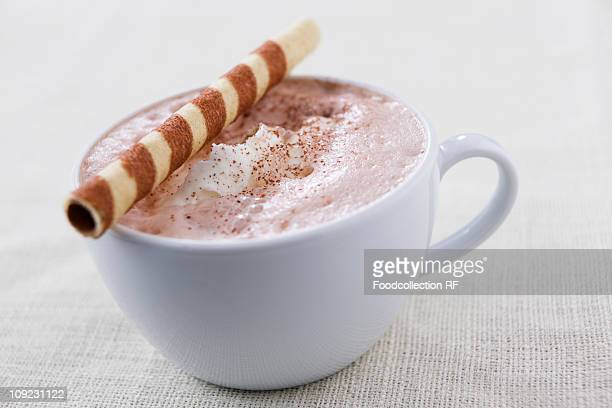 Cup of hot chocolate with wafer roll, close-up