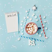 Cup of hot cocoa or chocolate, stylish fir tree and wish list on turquoise confetti background top view. Christmas or new year concept. Flat lay.