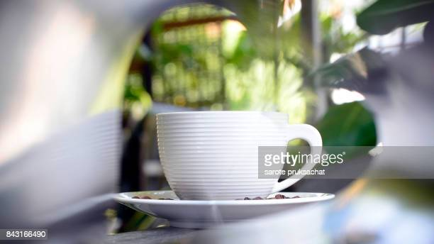 Cup of hot coffee and green nature background .