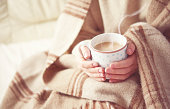 warm cup of hot coffee warming in the hands of a girl