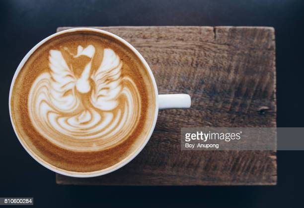 A cup of hot coffee with latte art on the surface.