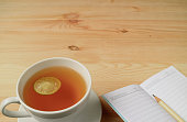 Cup of Hot Lemon Tea and Lined Note Papers with Pencil on Natural Color Wooden Table, with Free Space for Text and Design