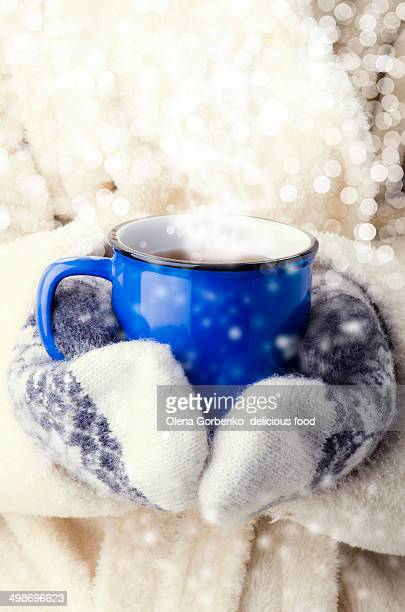 cup of hot tea in her hand wearing mittens.