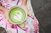 A cup of Matcha latte green tea is held on the hands of a woman wearing a beautiful kimono.The concept of local drinks in Japan.