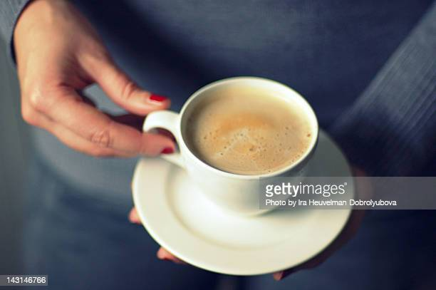 Cup of milk coffee in hands of young woman