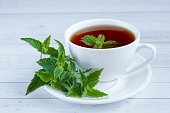 Cup of mint tea and a bunch of mint on the table.
