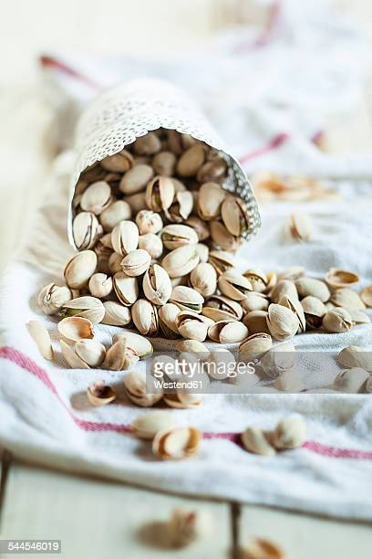 Cup of roasted and salted pistachios on kitchen towel