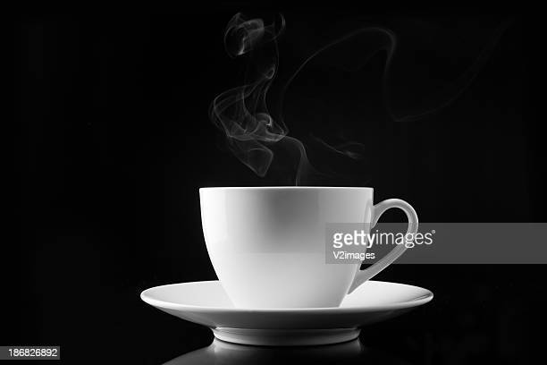 A cup of smoking hot coffee on a black background