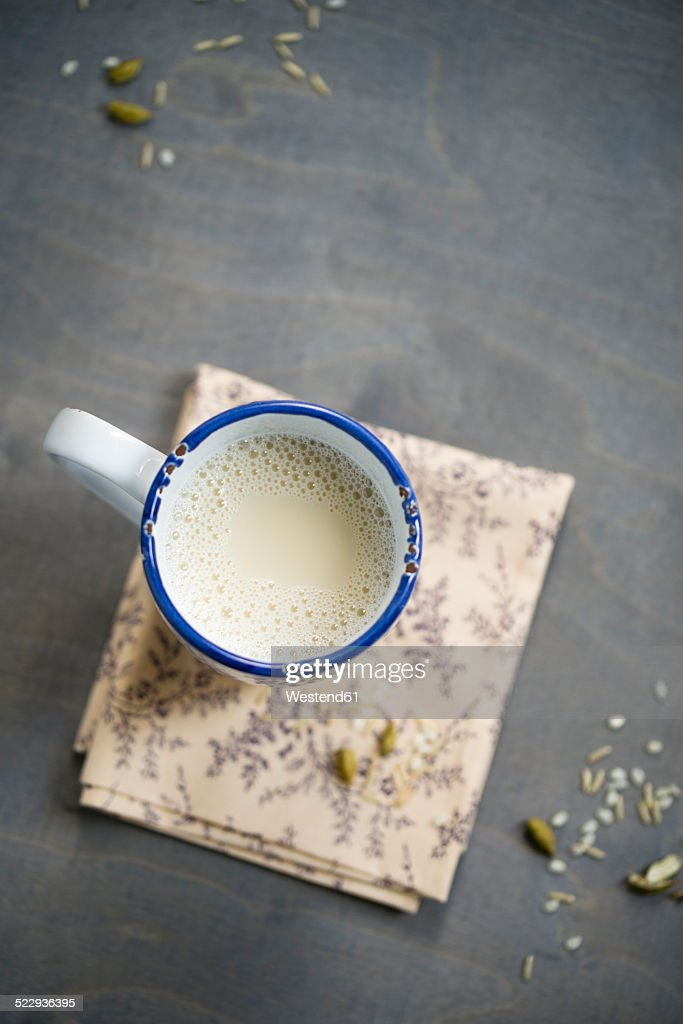 Cup of soy rice milk with cardamom and cinnamon on napkin aund wood, elevated view