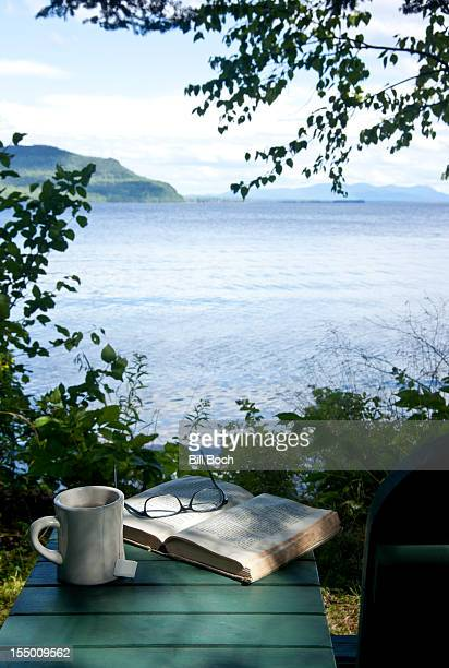 A cup of tea and a book by a lake