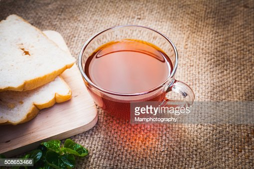 Cup of tea and bread on brown sack : Stock Photo