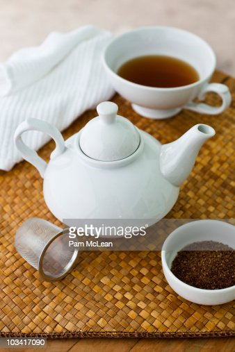 Cup of tea and teapot on woven mat : Stock Photo