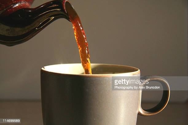 Cup of tea being poured from brown teapot