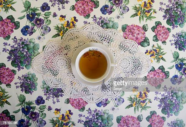 A cup of tea on a floral tablecloth