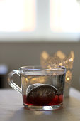 Cup of hot water with tea infuser. Candle holder in the background. Selective focus.