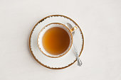 An old fashioned (vintage) cup of tea and a silver spoon on a white background taken from directly above.