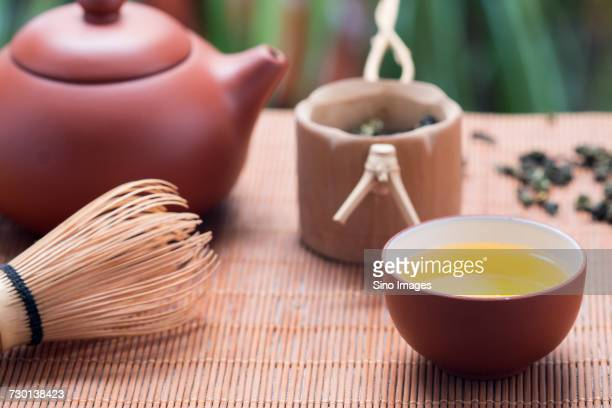 Cup of tea, tea whisk, teapot and mug with dried green tea leaves, China