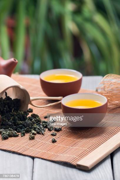 Cup of tea, tea whisk, teapot and mug with dried green tea leaves lying on tray, China