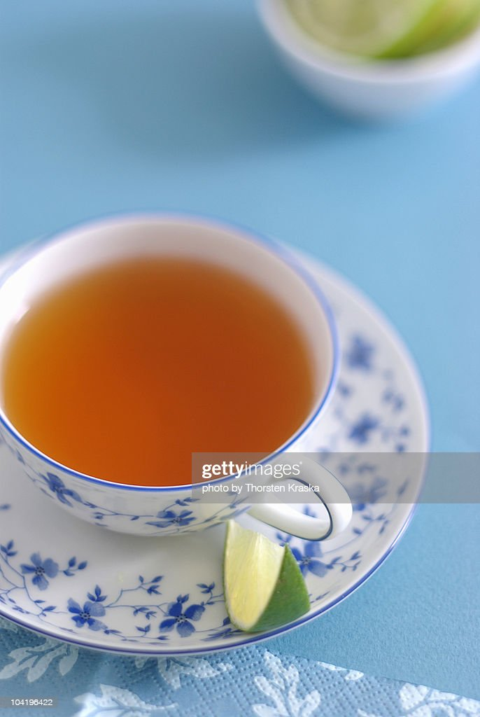 A cup of tea with a lime wedge