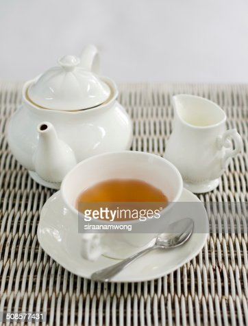 Cup of tea with little milk jar and teapot : Stock Photo
