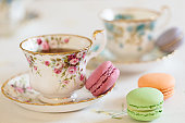Two cups filled with tea and some macaroons