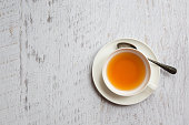 White cup of tea with metallic spoon on vintage white background, top view point