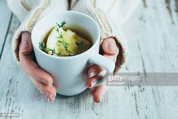 Cup of tea with thyme herb and lemon slices