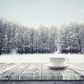 Hot drink in the cup on wooden table over winter snow covered forest. Beauty nature backgroundCup with hot drink on wood table over winter forest  background