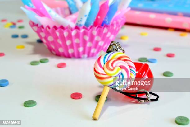 Cupcake container, candles sweets and colorful napkins on white background