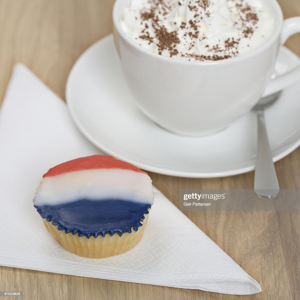 Cupcake decorated with flag and cup of hot drink : Stock Photo