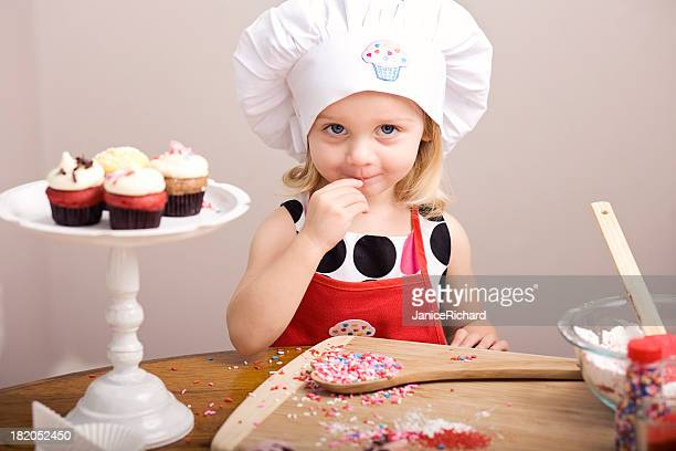 Cupcake Decorating by Little Girl in Chef's Hat and Apron