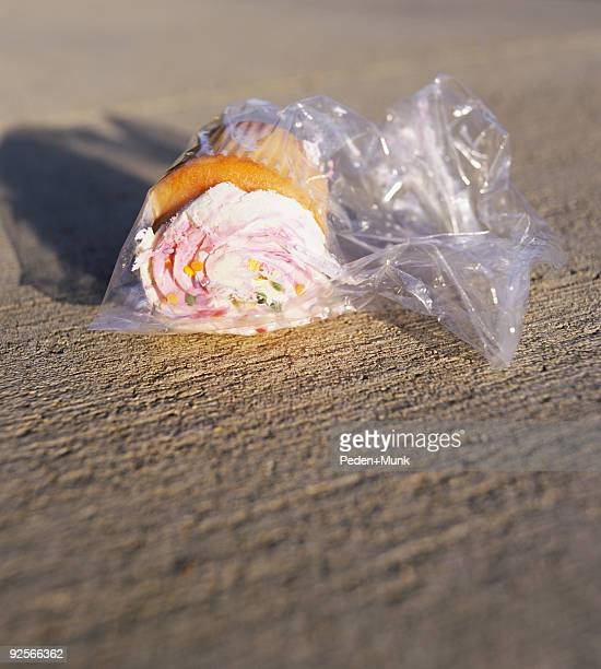 Cupcake in plastic bag on ground