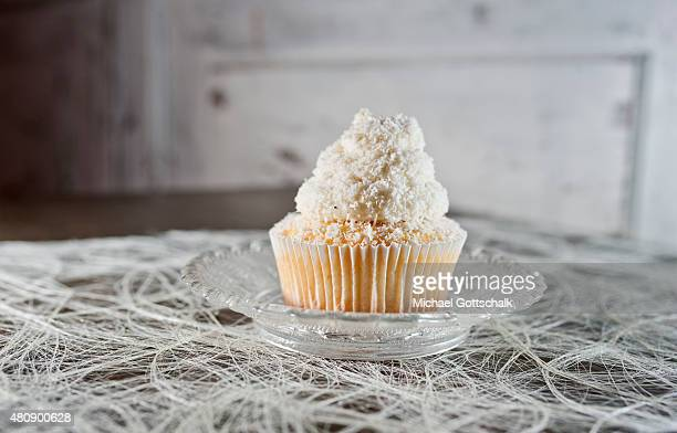 A cupcake with coconut flakes on a glass plate on July 15 2015 in Berlin Germany
