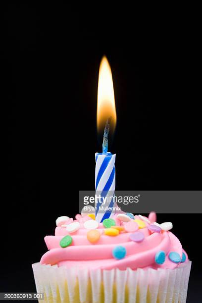 Cupcake with icing, sprinkles and candle