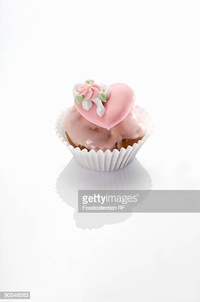 Cupcake with pink icing and sugar heart, close up