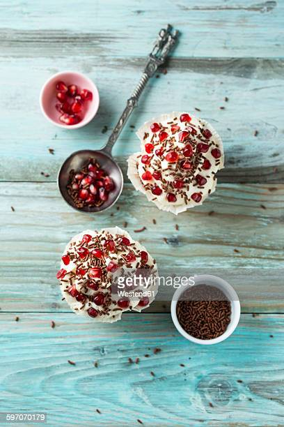 Cupcake with vanilla topping, pomegranate seeds and chocolate granules