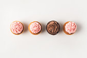 top view of set of arranged cupcakes with frosting isolated on white