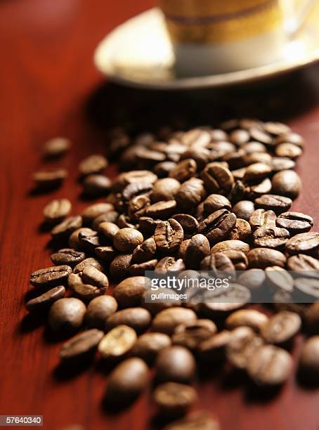 Cups of coffee and beans on a table.