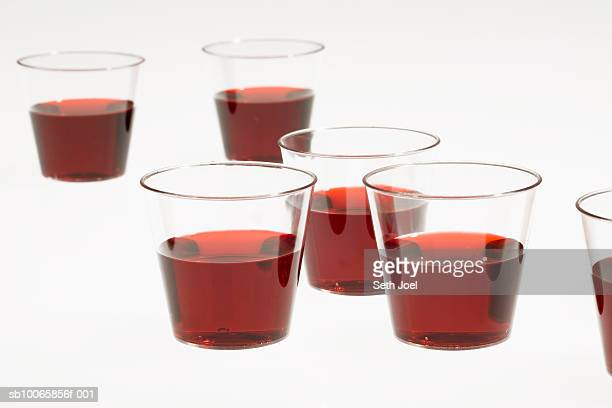 Cups with red liquid on white background