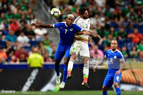 Curacao's midfielder Leandro Bacuna and Mexico's defender Jair Pereira jump for the ball as Curacao's forward Gino van Kessel watches during the...