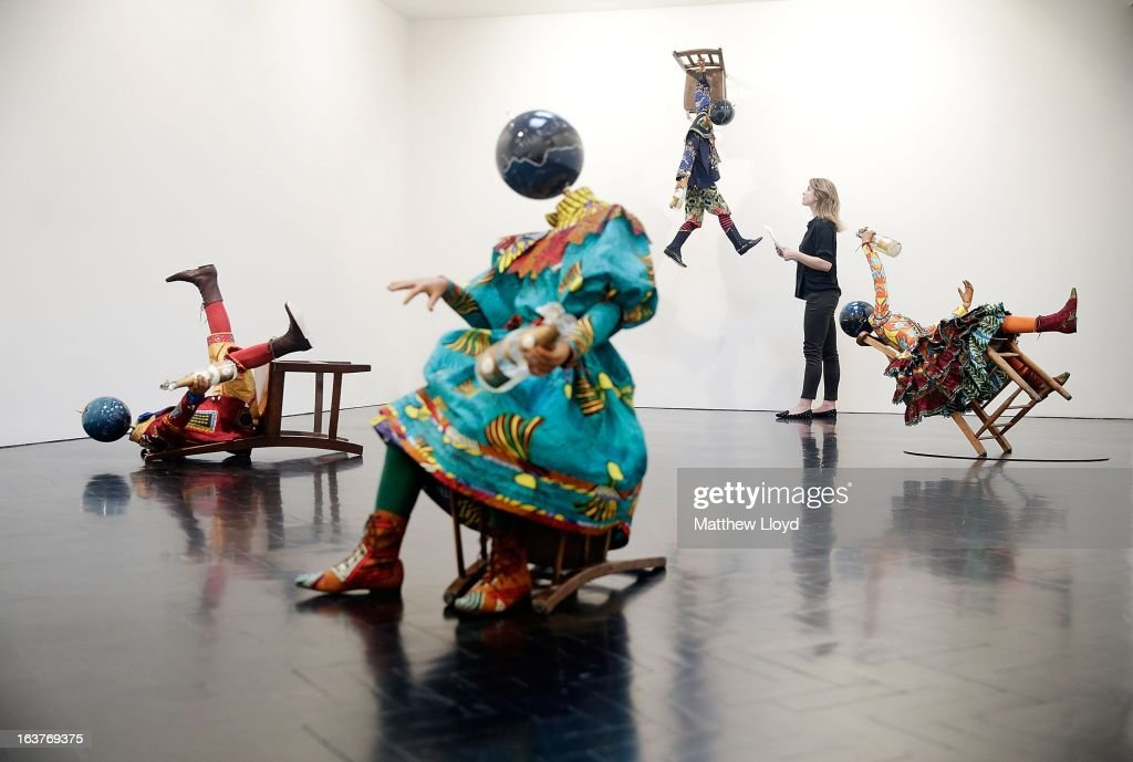 A curator poses alongside sculptures 'Champagne Kid (Fallen)', 'Champagne Kid (hanging)' and 'Champagne Kid (leaning)', part of the Pop! exhbition by Yinka Shonibare, MBE at the The Stephen Friedman Gallery on March 15, 2013 in London, England. The exhibition, which explores themes of corruption and excess, runs from 16th March to the 20th April 2013.