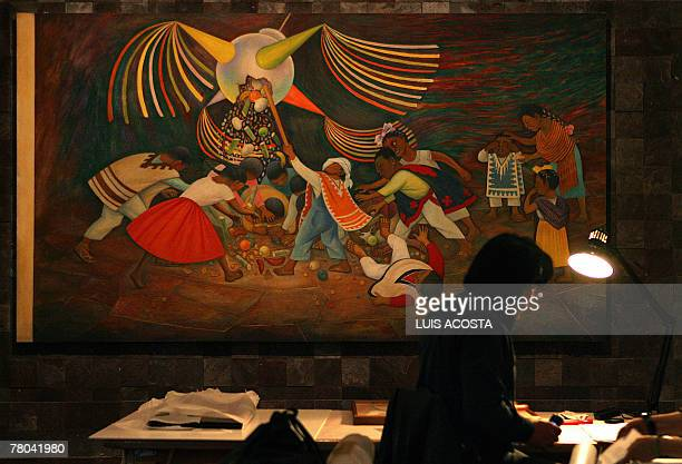A curator works next to the painting 'Piata' created by Mexican artist Diego Rivera during a presentation for the press at the Fine Arts Palace in...