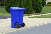 Large wheeled curbside recycling bin sitting at the end of a residential driveway on recycling day.  Curbside recycling programs are now available in many cities throughout the US.____________________