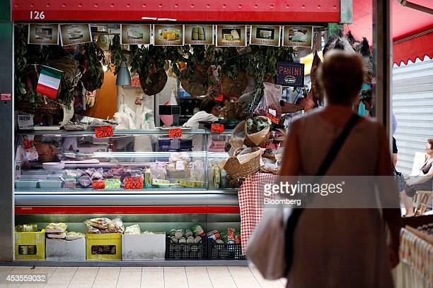 Cured ham legs hang above a stall as signs display the price in euros of meat and cheese goods at an indoor market in Rome Italy on Tuesday Aug 12...